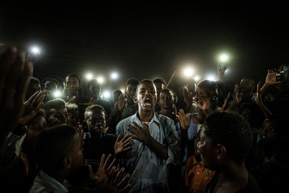 Un joven, iluminado por teléfonos móviles, recita un poema