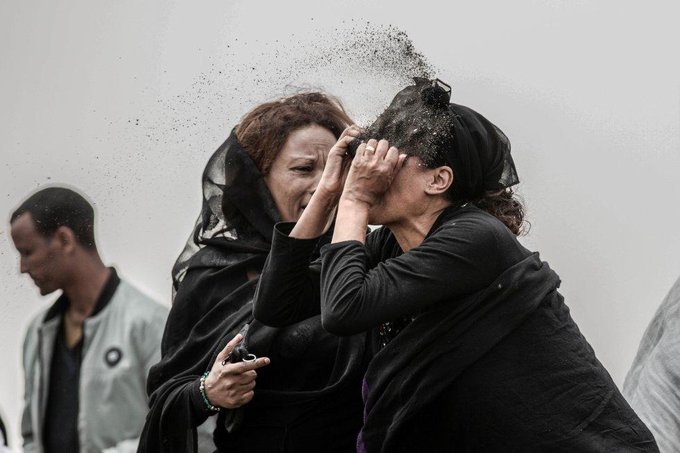 Un pariente de una víctima del accidente del vuelo ET302 de Ethiopian Airlines, arroja tierra en su cara