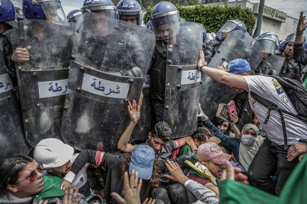 Unos estudiantes se enfrentan con la policía antidisturbios durante una manifestación antigubernamental en Argel
