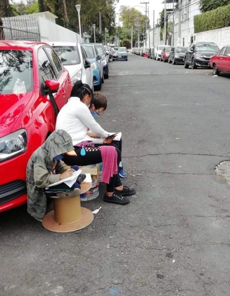 Conmueve en redes sociales madre que enseña a sus hijos a estudiar en la calle