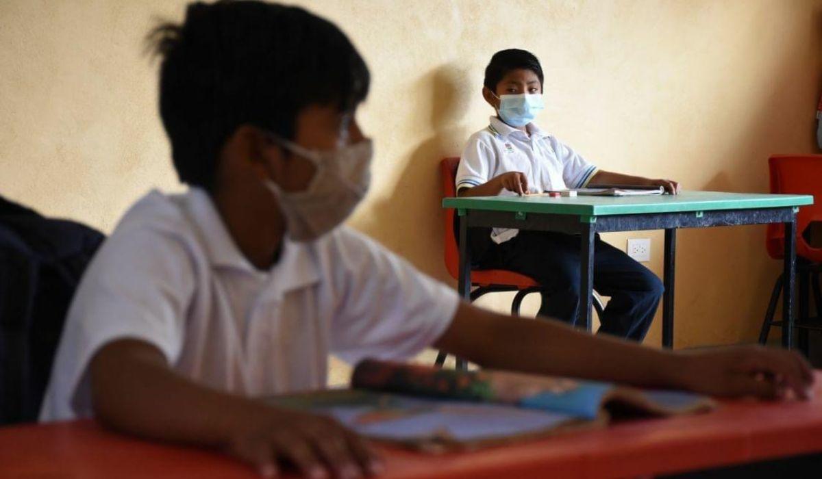 Los niños teniendo sana distancia en el salón de clases