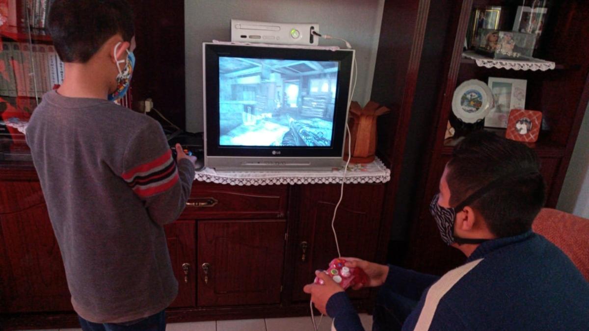 Dos niños jugando videojuegos en casa
