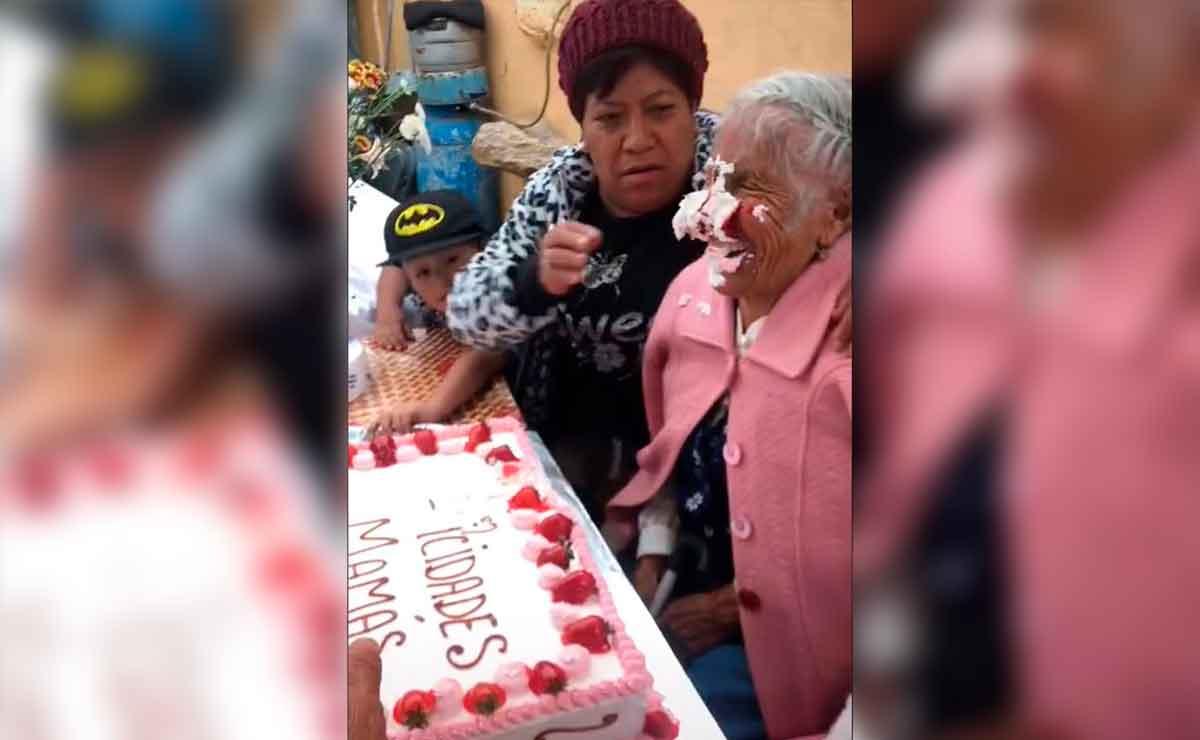Abuelita es empujada a pastel y se ríe.