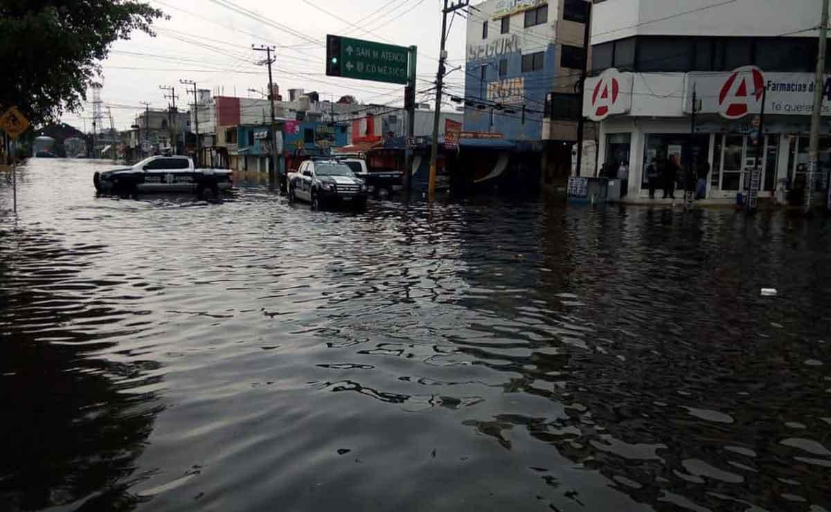 Gente atrapada en sus coches por fuertes lluvias en Metepec.