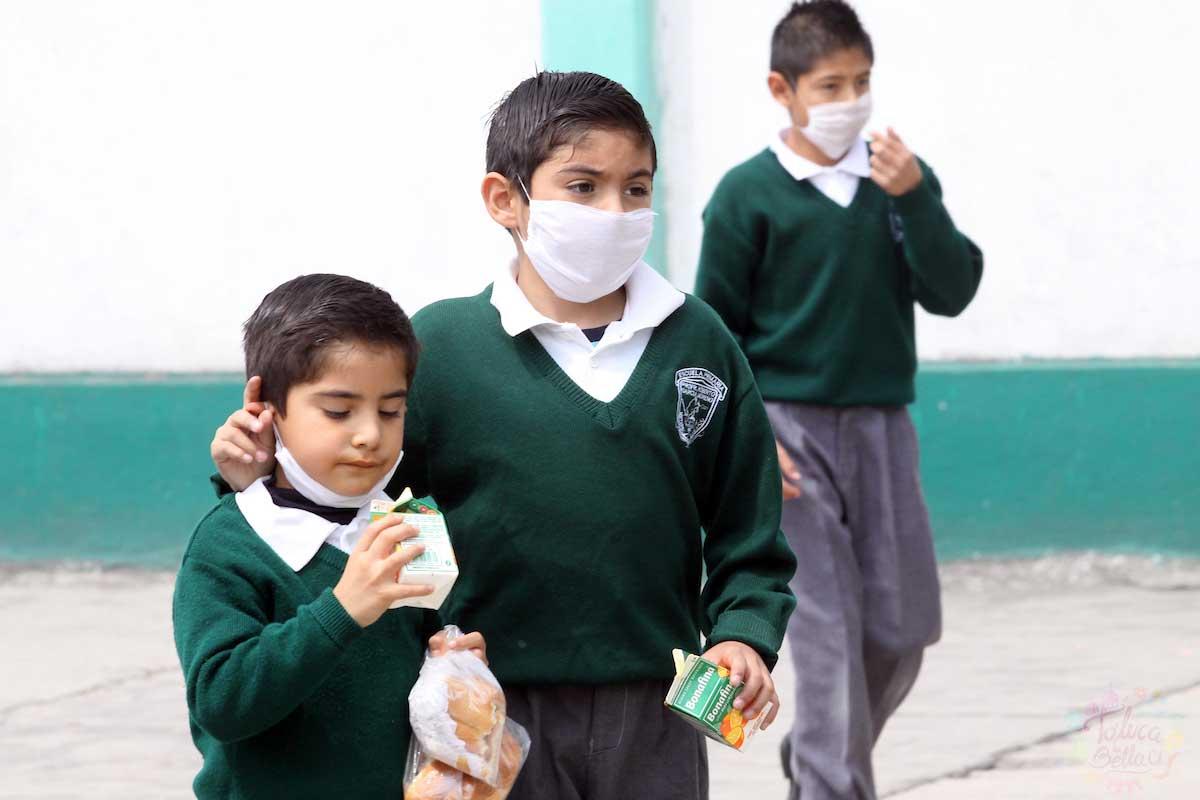 Niños usando cubrebocas dentro de las aulas de clase