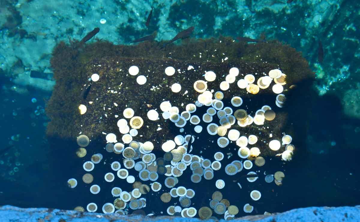 Monedas en la pila del atrio en Ojo de Agua.