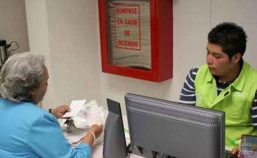 Esta es la fecha límite de pago de tenencia 2021 en Edomex. Mujer realizando pago de placas.