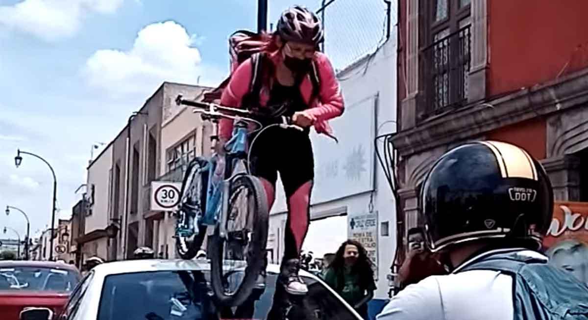 ciclistas protestan en querétaro y una se sube por encima de un auto