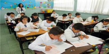 niños en salon de clases escribiendo apuntes