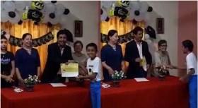 niño recibiendo su diploma de graduacion de primaria a lado de su familia