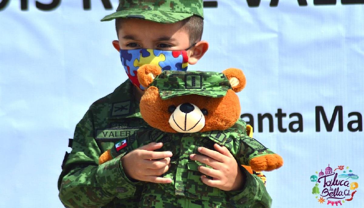 niño de cinco años con autismo se viste de soldado mientras abraza a su osito uniformado despues de cumplir su sueño de convertirse en soldado