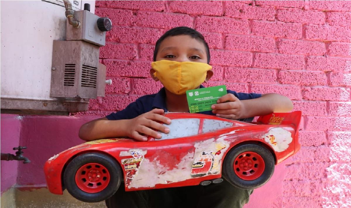 niño con auto de juguete recibiendo su tarjeta de mi beca para empezar
