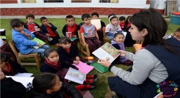 Maestra leyendo un cuento a niños y niñas de preescolar en jardín de niños edomex