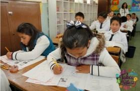 niños en salon de clases tomando apunte