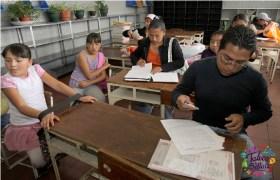padres de familia realizando trámites escolares en salón de clases en Edomex