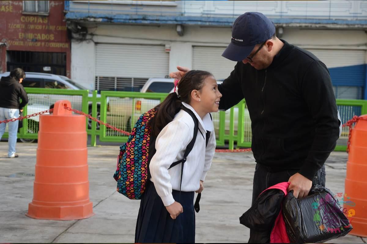 Padre de familia llevando a su hija a la escuela